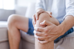 Man holding knee in need of PRP treatment for knee pain
