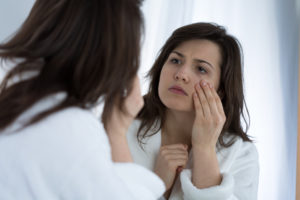 Woman looking at dark circles under the eyes in mirror