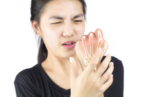 Woman holding hand with tendonitis pain